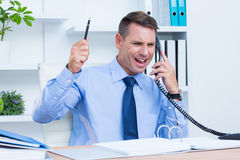 An angry businessman phoning at his desk Royalty Free Stock Photography
