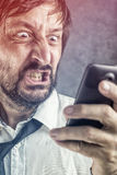 Angry businessman received frustrating SMS message Royalty Free Stock Photos