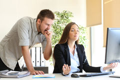 Angry businessman and relaxed businesswoman. Angry businessman hating to his relaxed colleague at office Stock Photography