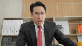Angry businessman scolding and yelling at camera in Office. Slow motion stock video