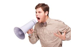 Angry businessman screaming with loud-speaker. Young handsome angry businessman screaming and holding loud-speaker, isolated on white background Royalty Free Stock Images