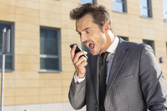 Angry businessman screaming at mobile phone against office building Royalty Free Stock Photos