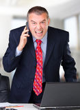 Angry businessman screaming into the mobile phone. Frustrated businessman screaming into the mobile phone while in the office Stock Photos