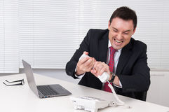 Angry businessman screaming at phone Stock Photography
