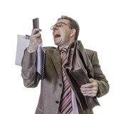 Angry businessman screaming at smartphone on white background. Portrait of busy and angry businessman screaming at smartphone, isolated on white background Stock Images