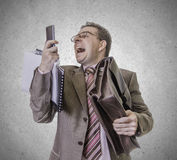 Angry businessman screaming at smartphone on white background. Portrait of busy and angry businessman screaming at smartphone,  on white background Stock Image