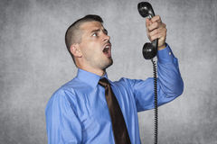 Angry businessman screaming during a telephone conversation. Angry business man screaming during a telephone conversation Royalty Free Stock Photo