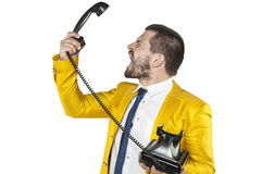 Angry businessman screaming to the telephone handset. Angry business man screaming to the telephone handset Royalty Free Stock Photography