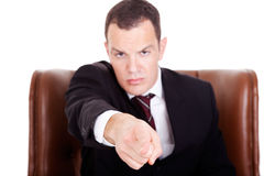 Angry businessman seated on a chair, pointing Royalty Free Stock Image