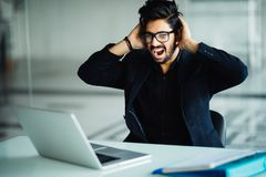 Angry indian businessman shaking his laptop computer and yelling in fury as he sits at his desk in the office royalty free stock photography