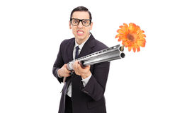 Angry businessman shooting flowers from a rifle Royalty Free Stock Photography
