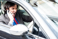 Angry businessman shouting while driving. Angry young male communicating through mobile phone while driving Royalty Free Stock Image