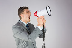 Angry businessman shouting through megaphone Stock Image