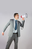 Angry businessman shouting through megaphone Stock Photography