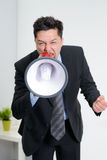 Angry businessman shouting on a megaphone Stock Image