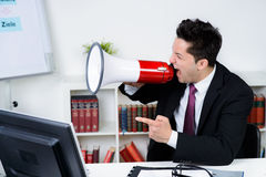 Angry businessman shouting on a megaphone Royalty Free Stock Image