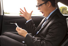 Angry businessman shouting on the phone with gesture. On the car Stock Photography