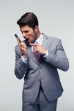 Angry businessman shouting on the phone. Over gray background Stock Photo