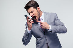 Angry businessman shouting on the phone. Over gray background Royalty Free Stock Photography