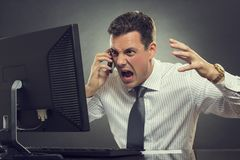 Angry businessman shouting on phone. Angry businessman in white shirt and necktie shouting and gesturing during cellphone conversation in front of a computer Stock Photography