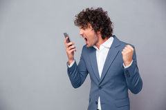 Angry businessman shouting on smartphone. Portrait of angry businessman shouting on smartphone over gray background Stock Photo