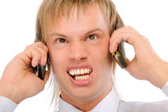 Angry businessman shouts in two phones Royalty Free Stock Image