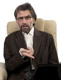 Angry businessman sitting in chair with notebook Stock Photography