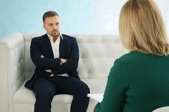 Angry businessman sitting on couch talking to female psychologist stock images