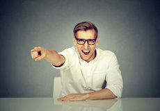 Angry businessman sitting at desk screaming Stock Photography