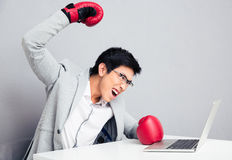 Angry businessman sitting at the table in boxing gloves Stock Photo