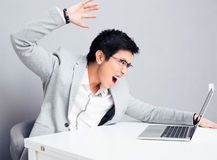 Angry businessman sitting at the table with laptop Royalty Free Stock Photo