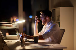 Angry businessman with smartphone at night office Stock Photo