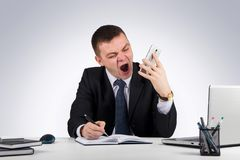 Angry businessman with smartphone shouting on gray background. Office, finances, internet, business, success and stress concept-Angry businessman with smartphone Royalty Free Stock Photos