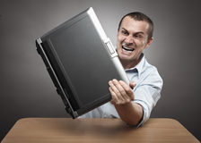 Angry businessman smashing his laptop. Extremely angry businessman smashing his laptop on the desk Royalty Free Stock Photos