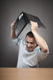 Angry businessman smashing his laptop. Extremely angry businessman smashing his laptop on the desk Royalty Free Stock Images