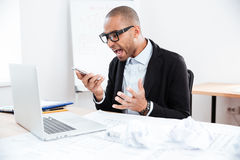 Angry businessman in stress talking on mobile phone Royalty Free Stock Photo