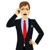 Angry businessman talking on mobile phone Royalty Free Stock Image