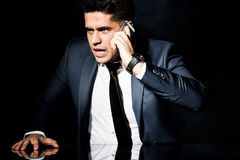 Angry businessman talking on phone Royalty Free Stock Image