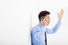 Angry businessman talking on the phone in office Royalty Free Stock Image