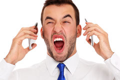 Angry businessman talking on two phones royalty free stock images