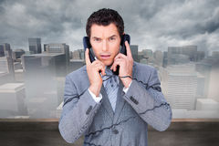 Angry businessman tangle up in phone wires Stock Photos