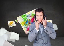 Angry businessman tangle up in phone wires Stock Photo