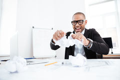 Angry businessman tearing up a document in office Royalty Free Stock Images