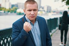 Angry businessman threaten with a fist. Outdoors portrait royalty free stock images