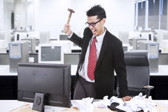 Angry businessman throw hammer at computer Stock Images