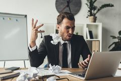 Angry businessman throwing crumpled papers. At modern office stock photo