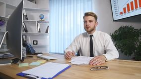 Angry businessman throwing crumpled papers while working at his workplace in office stock video