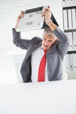 Angry businessman throwing his laptop. In his office Stock Images