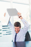 Angry businessman throwing his laptop. In his office Stock Photography