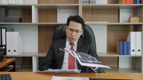 Angry businessman throwing papers into camera. stock footage